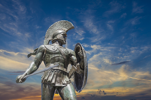 Metal statue of a Roman soldier with sword and shield in front of sunset