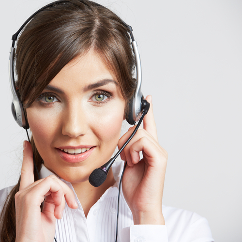 Female employee in a white button-front shirt with a headset on