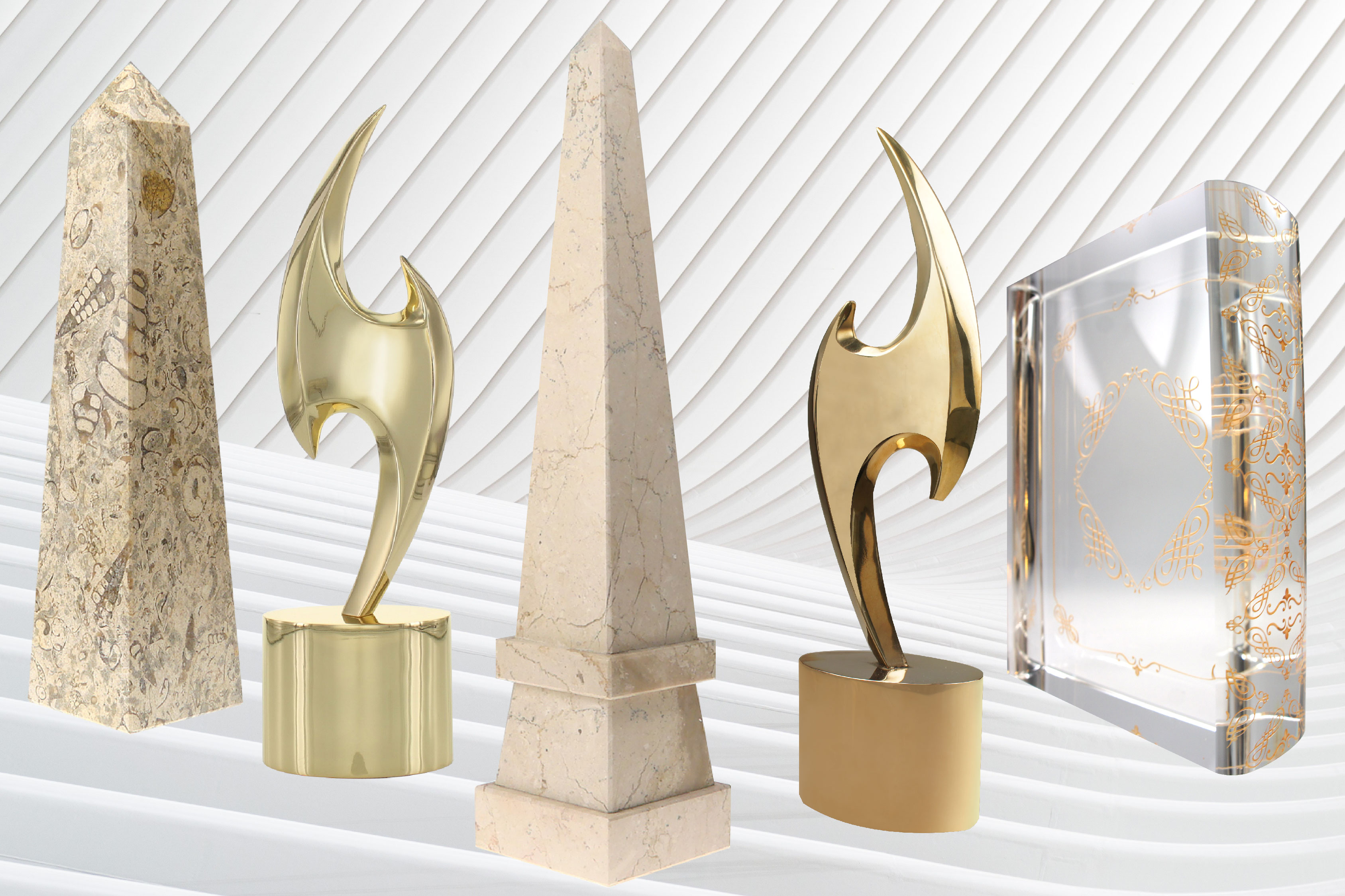 5 luxury objets d'art from the Society Awards Exclusives Collection. From left to right, Fossil Stone Obelisk, Society Star, Boticino Marble Stepped Obelisk, Polished Bronze Society Star, SA Crystal Book