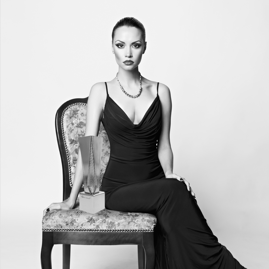 Model in black evening gown, sitting on a damask side chair with the Gatsby Silver Small award from the Exclusives Line of trophies.