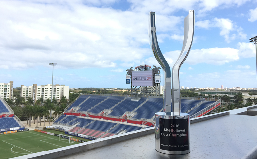 FIFA SheBelieves Champion Cup sitting on a ledge overlooking a soccer stadium. Designed by Gabrielle Rein of Viceroy Creative.