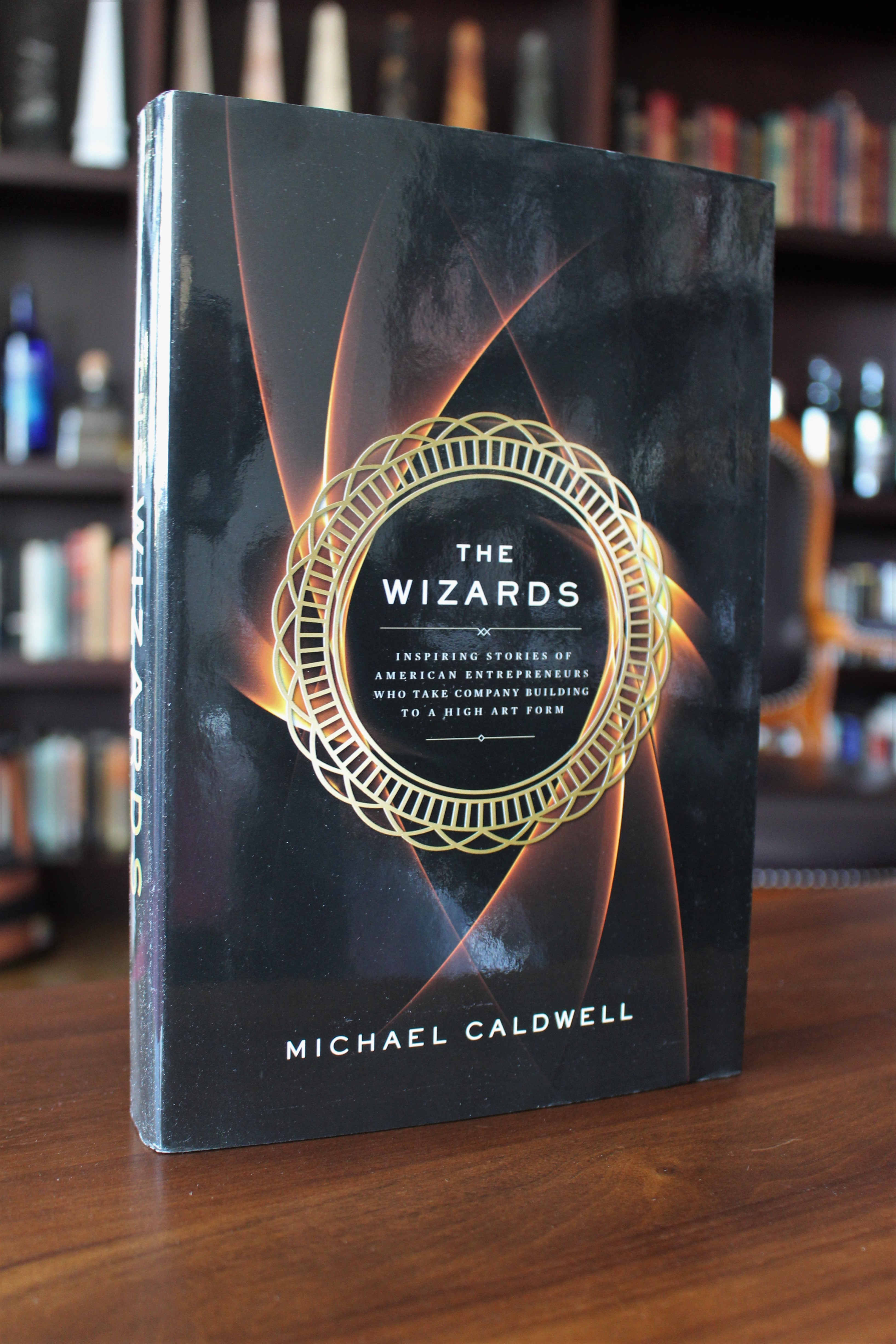 Book cover of The Wizards by Michael Caldwell on a table in our office Whiskey Library