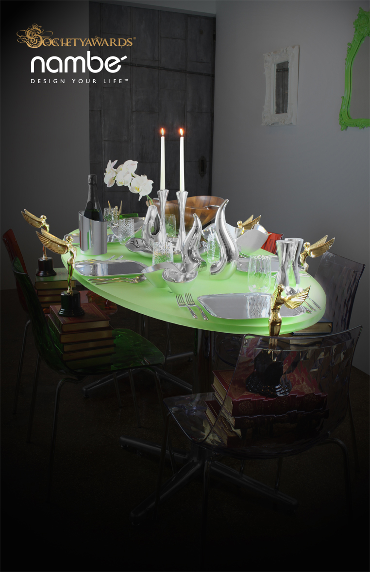 Green dining table set with pieces from the Nambé collection of luxury tableware goods. At each seat around the table is a Society Angel award