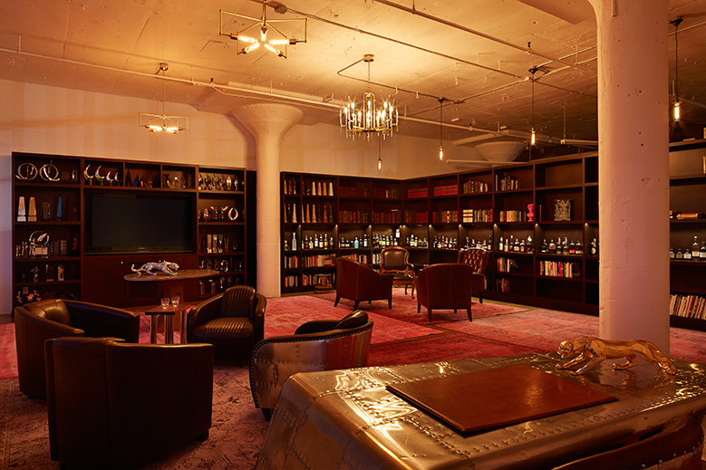 Wide view of our Whiskey Library with overdyed rugs, leather chairs, hanging brass light fixtures, custom wood shelves