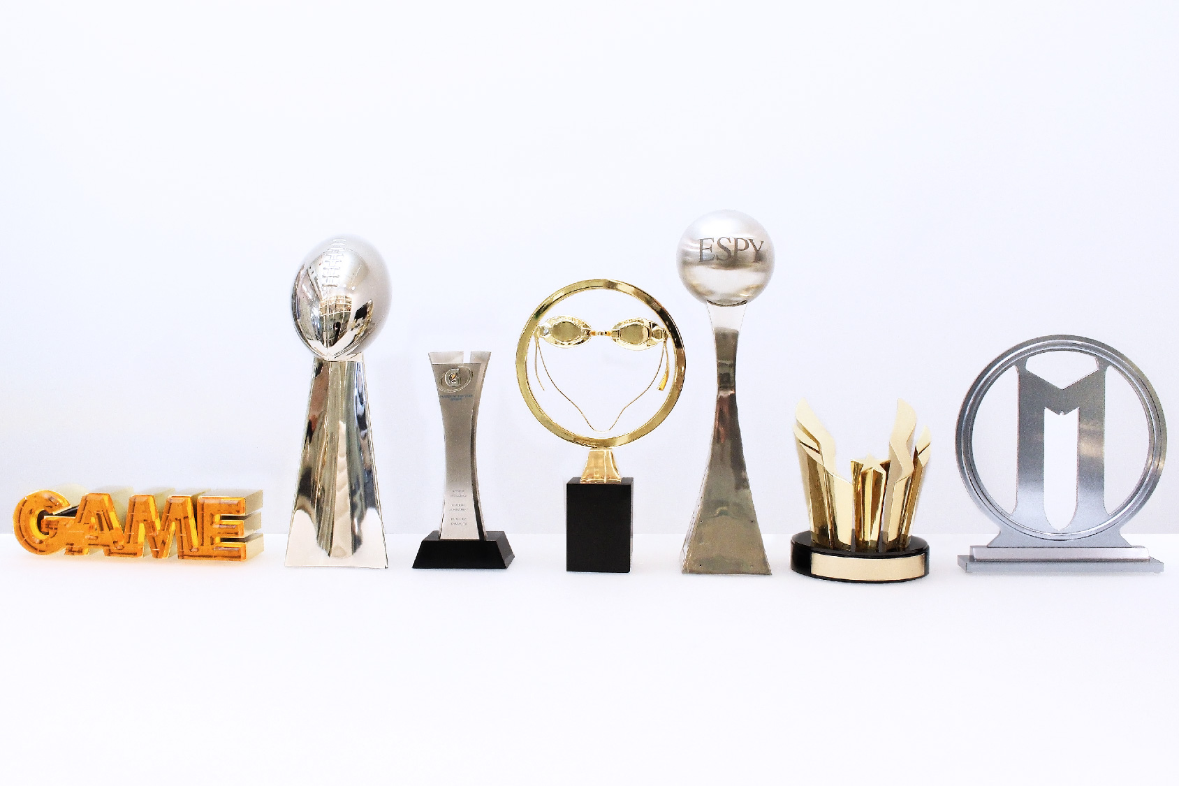 Six custom sports trophies by Society Awards grouped in a line on a white table