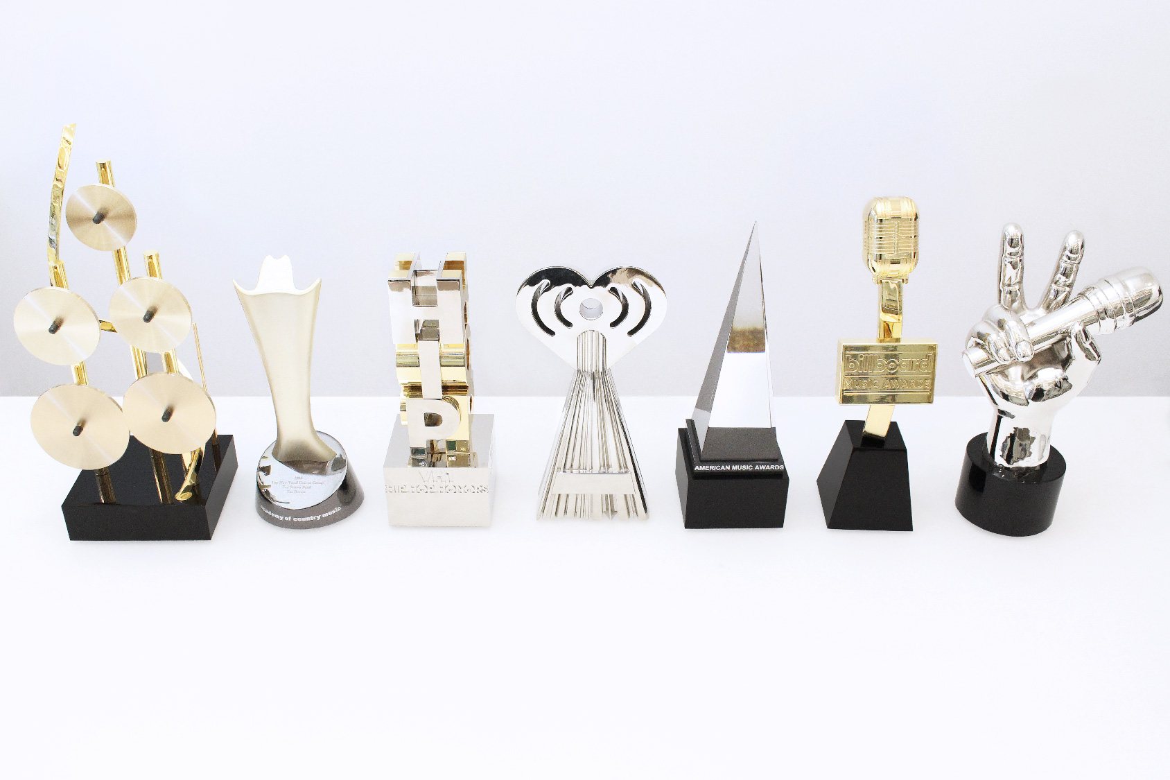 Front view of seven famous custom music awards program trophies, all crafted by Society Awards