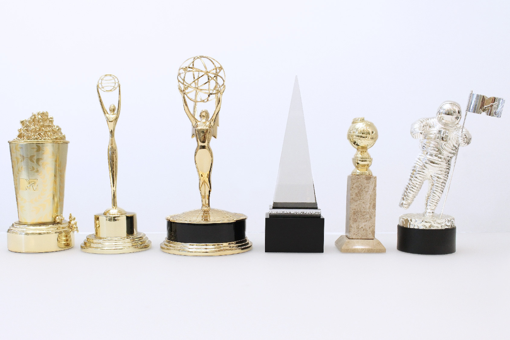 Six famous trophies on a white conference room table at the Society Awards New York offices