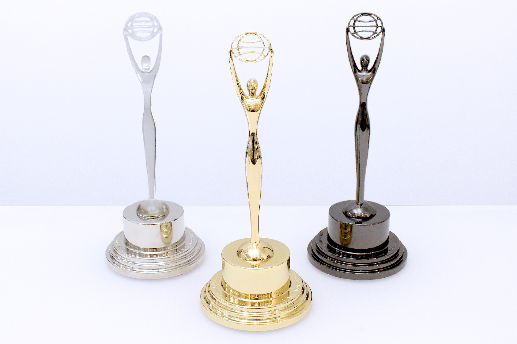 Three Clio trophies in crystal, gold and black displayed on a white table at Society Awards NYC headquarters