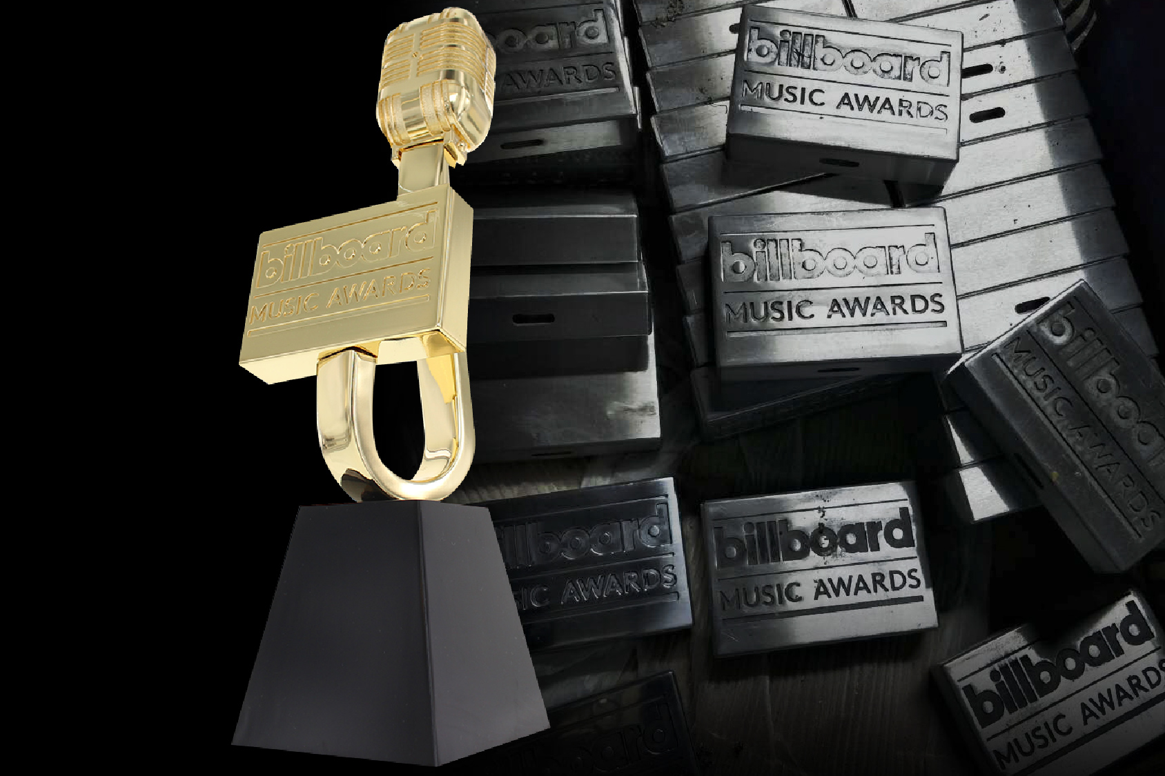 Billboard Music Awards trophy in front of machined plaques