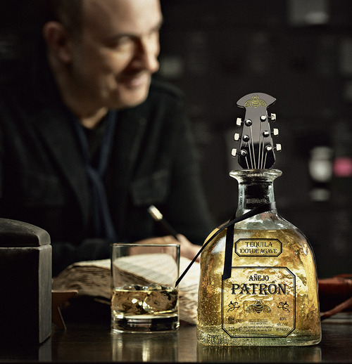 A bottle of Patrón Añejo with the limited edition guitar-head-shaped bottle stopper sitting on a table in front of designer John Varvatos