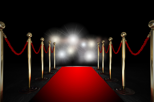 Red carpet with velvet ropes on either side and flashing lights of cameras in the distance.