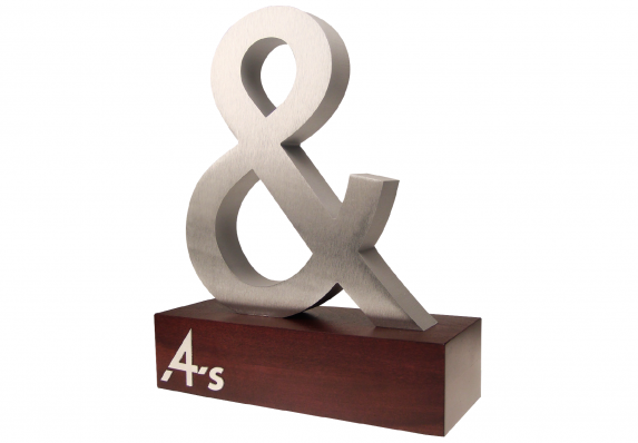 A custom machined aluminum ampersand mounted on a wood base.