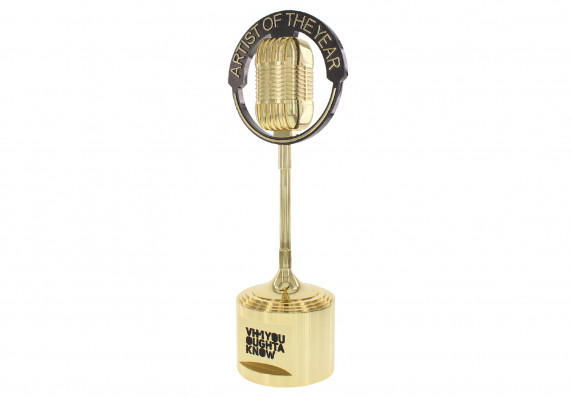 Gold metal microphone trophy presented to artist of the year at music awards show.