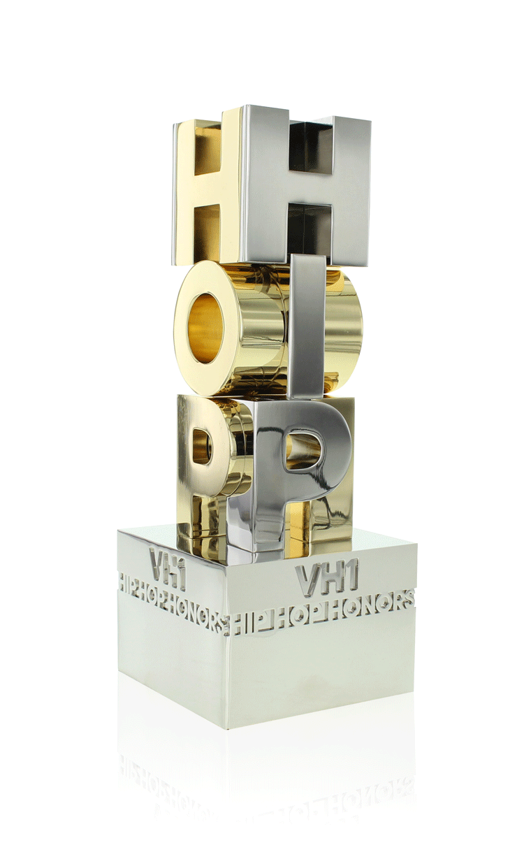 Pure aluminum award with intersecting letters and gold plating.