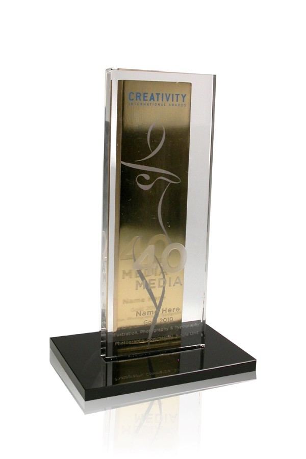Gold plated metal upright plaque with clear crystal plaque mounted on black base.