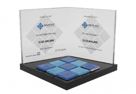Deal toy presented for an initial public offering. Has two clear plaques mounted on black base and blue tile detail