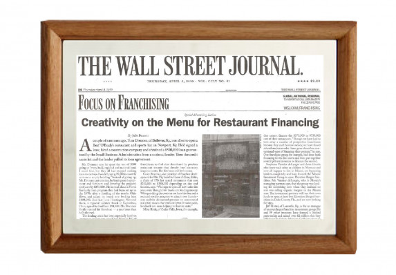 Framed issue of a Wall Street Journal page about a financial franchising deal. The frame is by Nambé and is crafted from wood and metal.