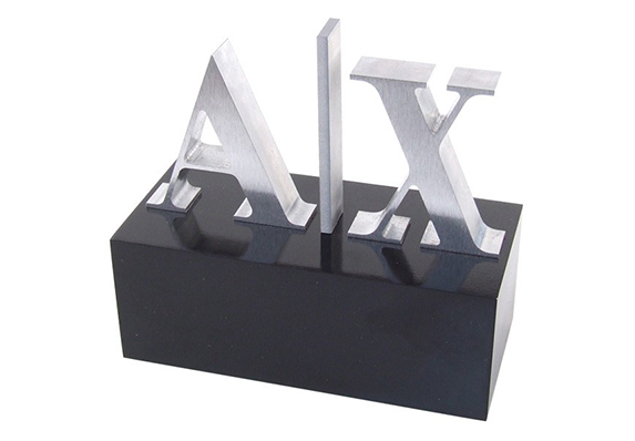 Armani Exchange logo trophy with machined cut out logo lettering on black acrylic base to honor employees with annual sales of one million dollars or more