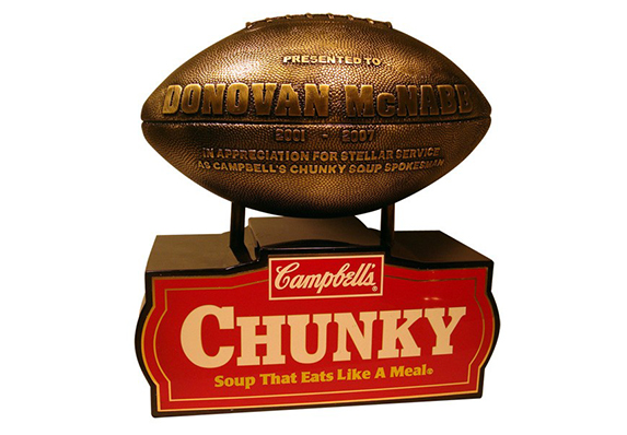 cast resin metal plated football with raised lettering on wood base with shiny brass screen printed plate