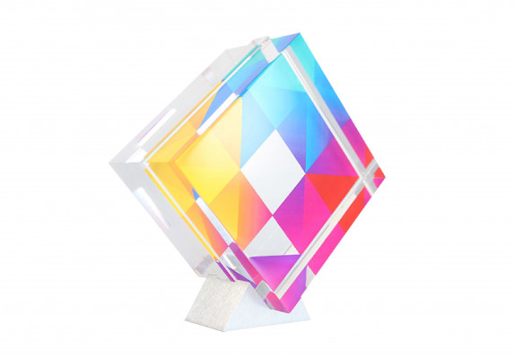 Acrylic award with colorful geometric pattern on an aluminum stand.