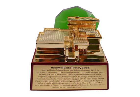 gold plated replica of a charity built school with green crystal mountain accent on cherry piano wood base