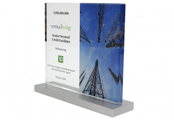 Crystal plaque deal toy with color image and financial transaction details mounted on metal base.