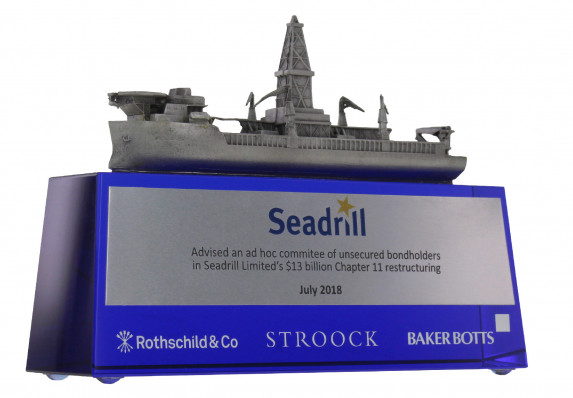 Model ship with fine detail is presented on a tapered blue crystal base for a chapter 11 restructuring deal toy. Includes color printed plate and etched logos.