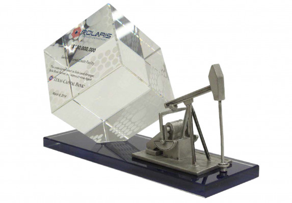 Crystal standing cube printed with tombstone text is mounted on a long black base which includes a silver model oil drill