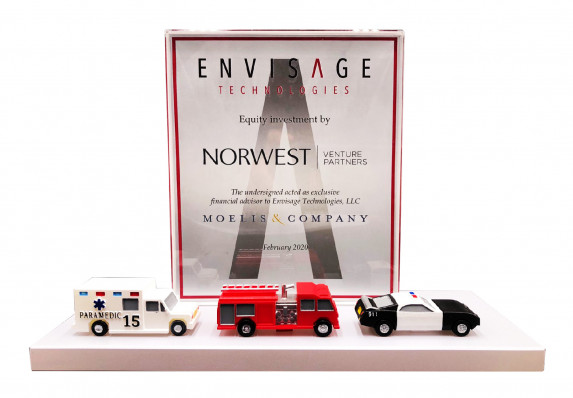 A custom financial tombstone crafted for an equity investment deal in a technology company. This unique deal toy includes three model emergency response vehicles.