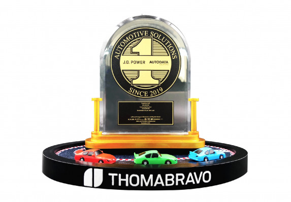 A custom, luxury financial tombstone with a crystal plaque, gold medallion and model cars.