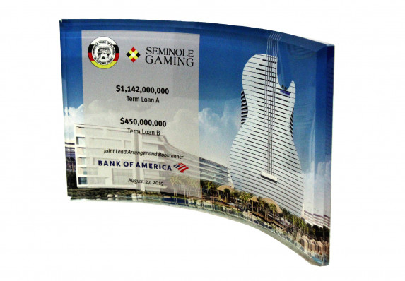 A bevel-edged curved crystal panel with reverse color printing is the canvas for the details of this large gaming industry financial transaction.