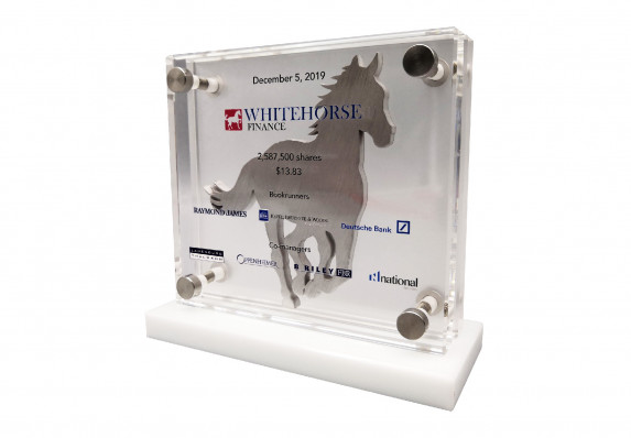 A custom deal toy with financial transaction details presented on a crystal plaque. This unique tombstone includes an elegant brushed aluminum stallion silhouette.