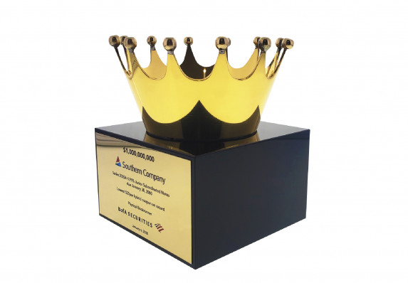 A shiny gold plated crown is mounted atop a modern black base in this elegant financial tombstone for a subordinated debt transaction.