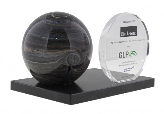 Color Logos Were Printed on a Crystal Plaque in this Unique Deal Toy. The Crystal is Mounted on a Modern Black Base with an Artful Sculpture. This Tombstone was for a Large Deal Involving the Acquisition of US Warehouses.