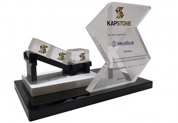 Model conveyor belt with logo etched boxes mounted on base with transaction tombstone for an acquisition deal.