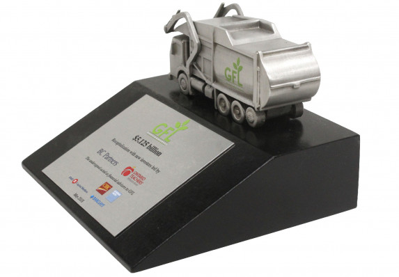 This unique deal toy features a cast metal garbage truck mounted on a black base with a color printed financial tombstone plate.