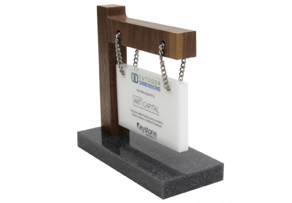 Tombstone crafted by Society Awards Finance Group for an M&A deal. The design incorporates a hanging plaque attached to a wood arm and base with chain.