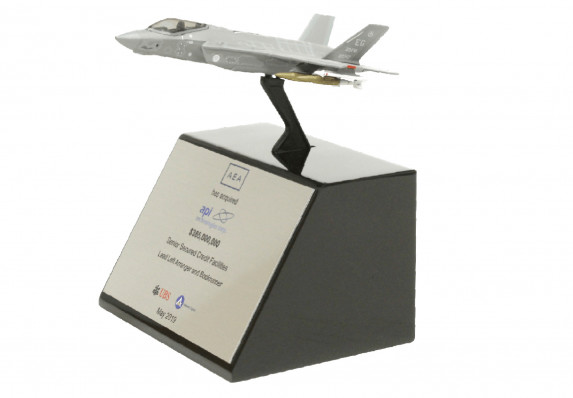 A model fighter jet is presented on an elegant tapered base in this exceptional financial tombstone for an acquisition deal.