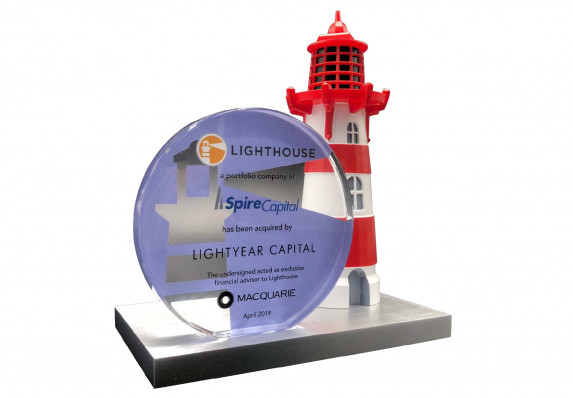 A financial tombstone printed on a color printed plaque and mounted on a base with a detailed model lighthouse.