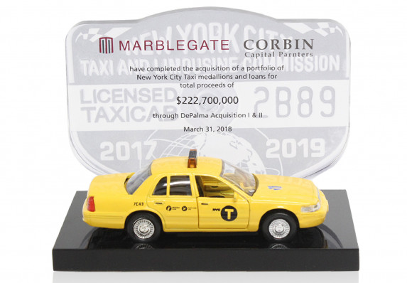 A custom tombstone crafted for the successful close of a deal to acquire a portfolio of taxi medallions. The design incorporates a model taxi and a transaction plaque with a mock medallion.