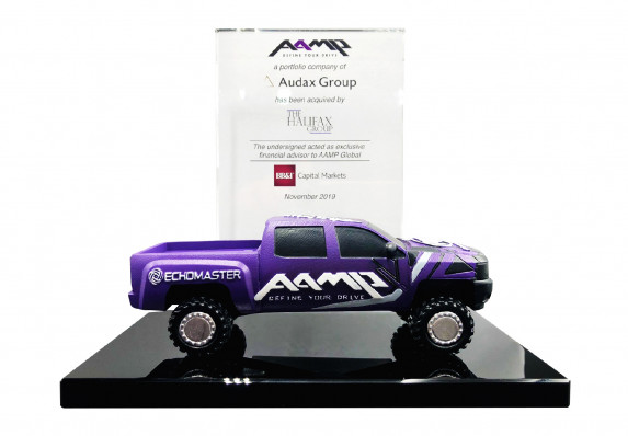 Custom acquisition deal toy with a model monster truck mounted on a black crystal base.