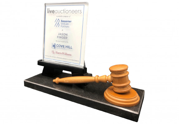 This custom deal gift combines an auctioneer's gavel and a crystal tombstone plaque on a black base to commemorate the sale of a portfolio company.