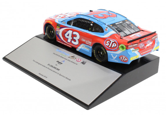 Custom deal gift with a large metal tombstone and brightly colored racecar model mounted on top. This luxury high-end tombstone commemorates the sale of an auto care division.