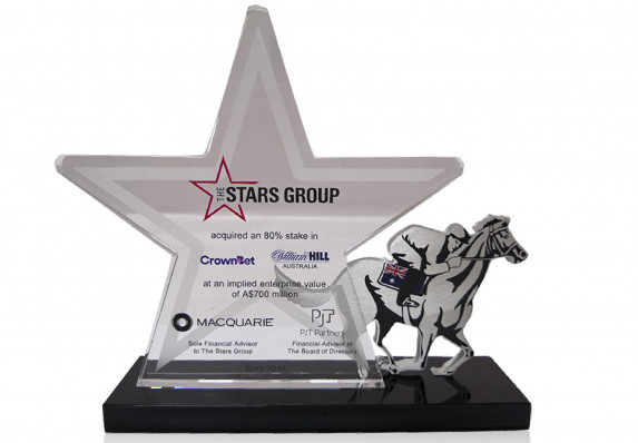 A custom star plaque with transaction details is mounted alongside a race horse with jockey in this stake acquisition deal gift.