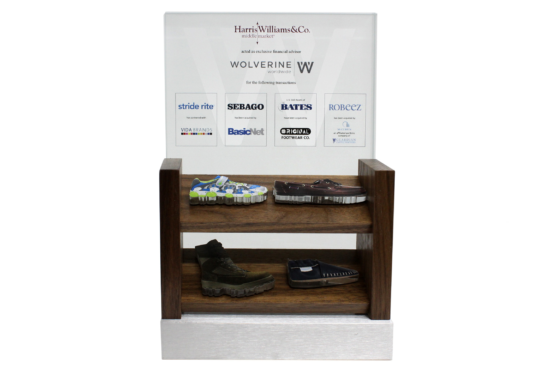 A detailed deal gift that incorporates a wood store shelf mock-up with color printed cut-out acrylic shoes. This tombstone was created for a complex, multi-acquisition deal.