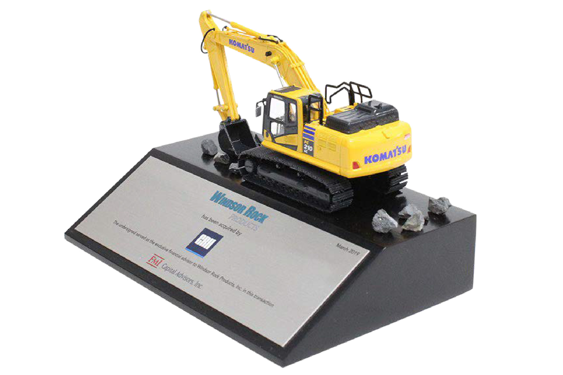 A scale model yellow digger vehicle mounted on a tapered black base with a silver financial tombstone plaque.